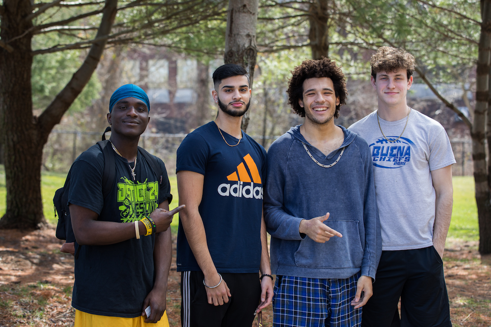 Four male students stand shoulder to shoulder, smiling.