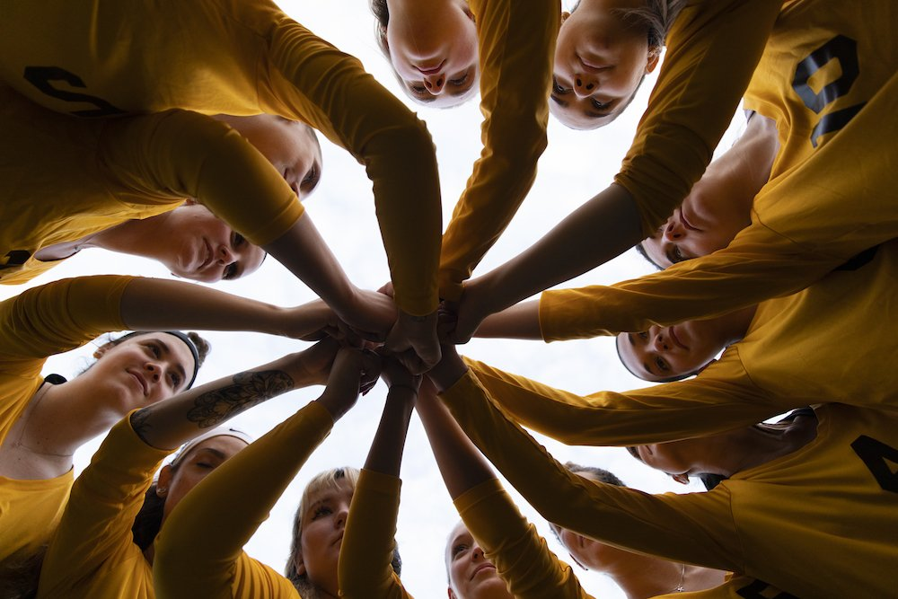 a group of volleyball athletes with their hands all together.