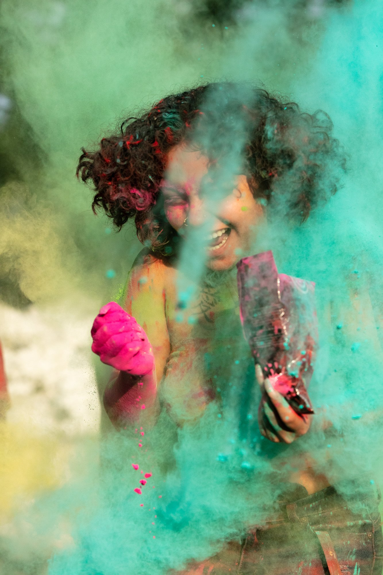 female student with curly hair smiles broadly as she's covered with blue powder paint.