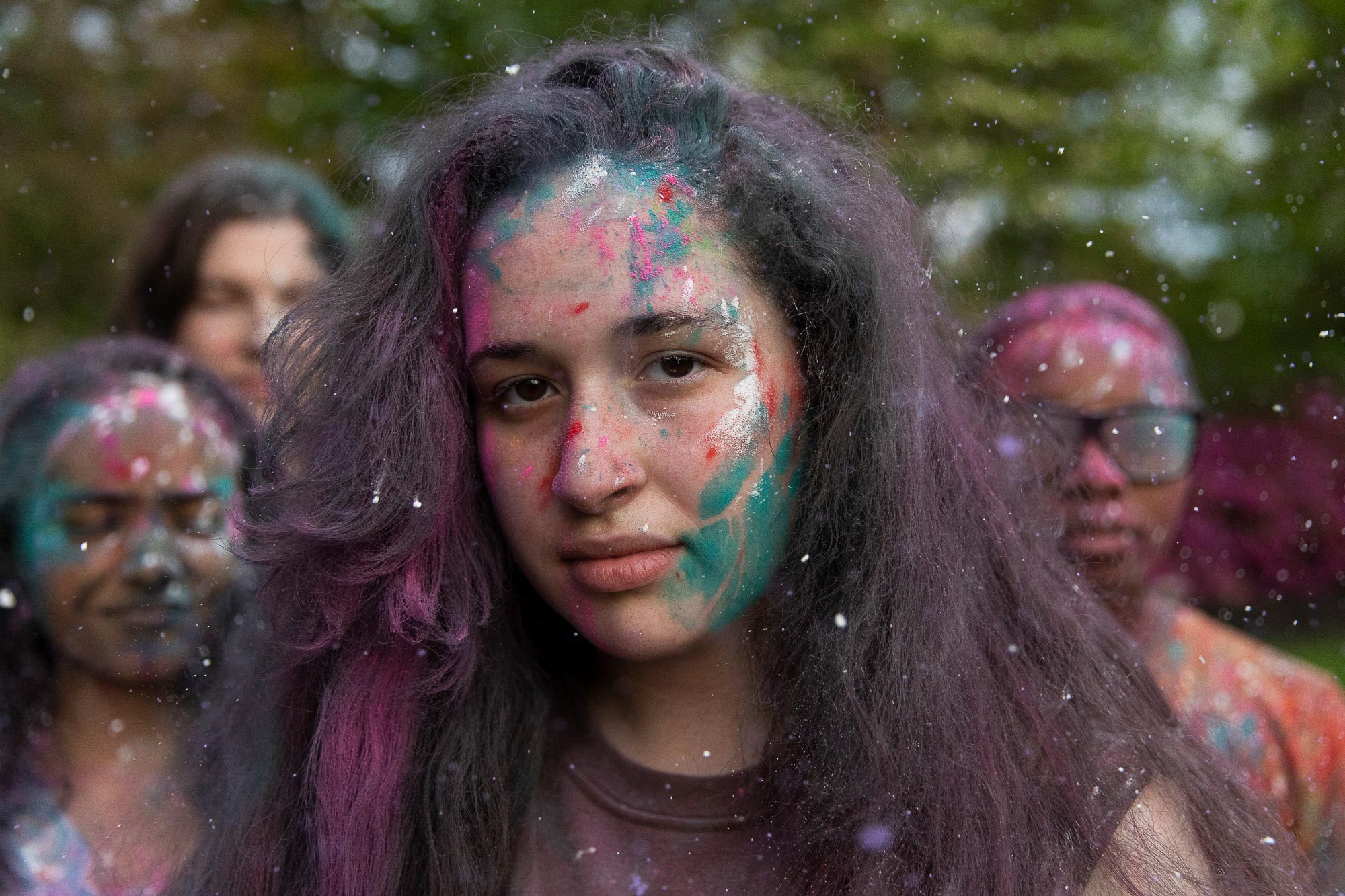 A close up portrait of a female with paint on her face