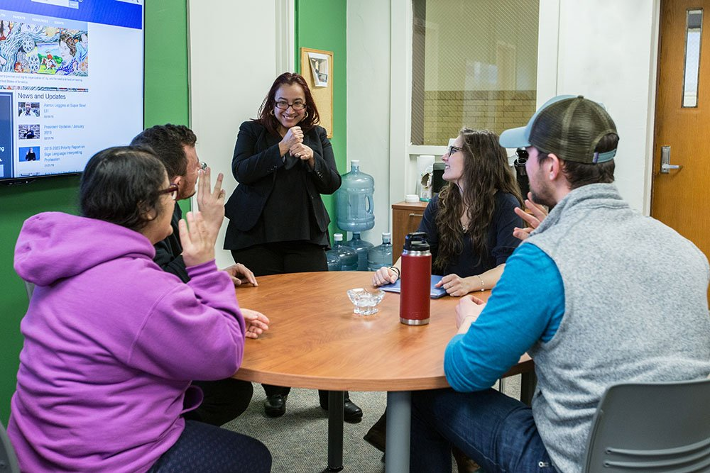 Small group of sign language students sitting at a conference table while professor stands and signs with them.