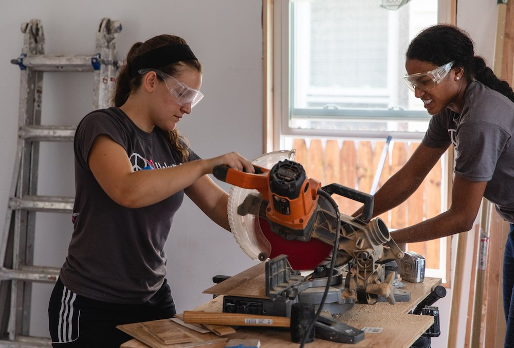 Two students work together with a saw.