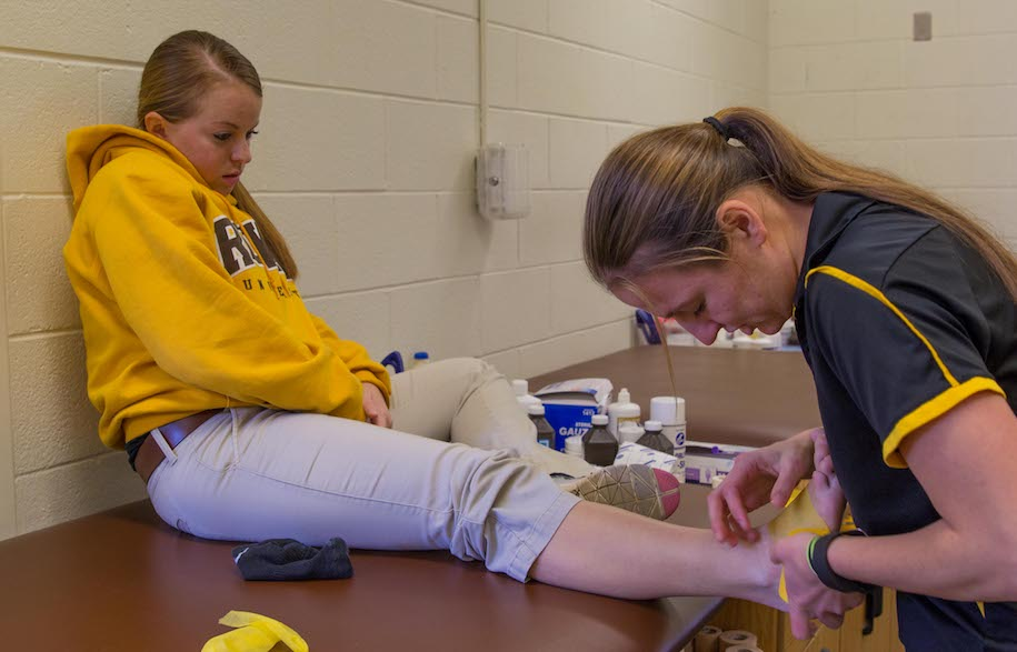 A student wrapping another student's ankle