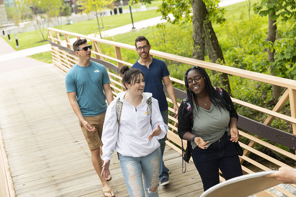 students walking across a bridge.