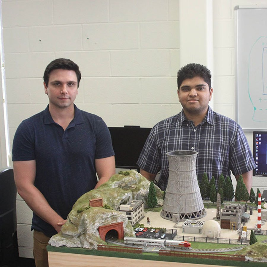 John S. standing next to a partner and one of his computer science projects
