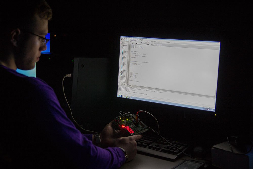Student in dark room looking at a computer screen.