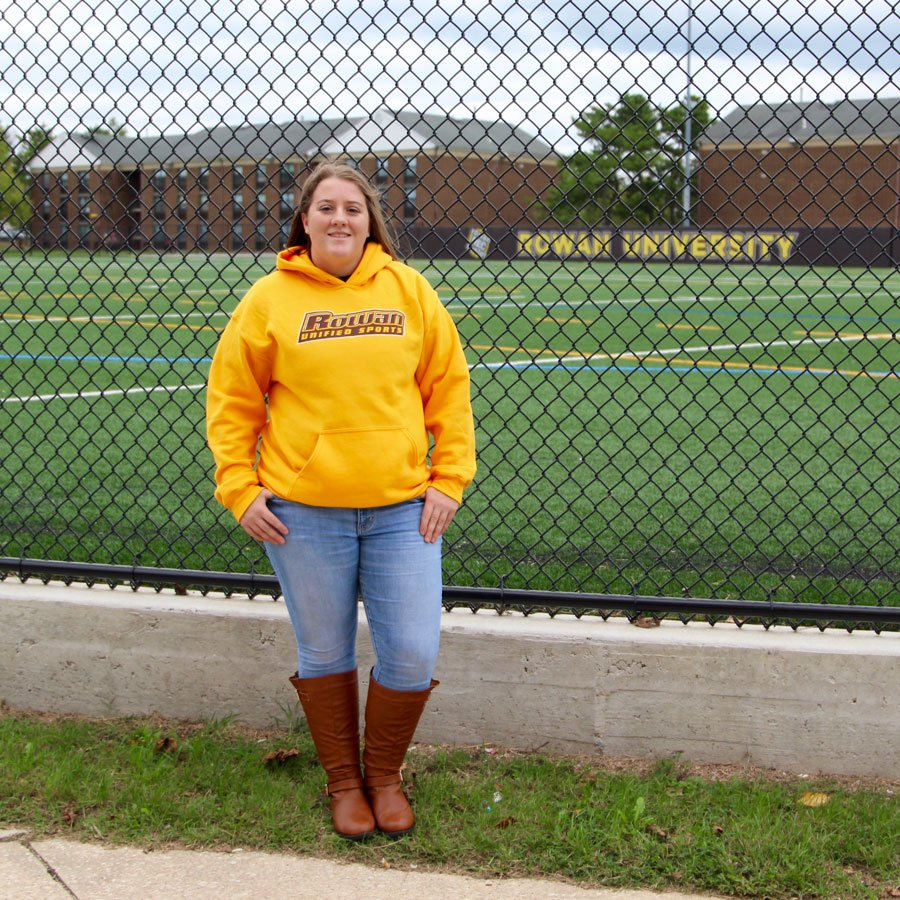 Maribeth stands outside of a brick dorm at Rowan University with her left hand on her hip, wearing a gray #RowanPROUD t-shirt.