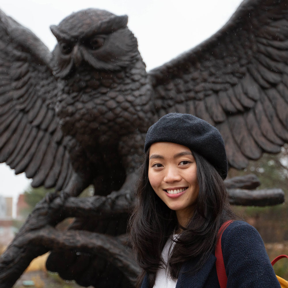 Nam stands in front of the Rowan owl statue.