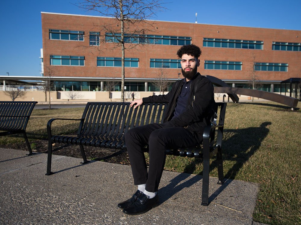 Physics major Nabil J. sits on a bench on campus