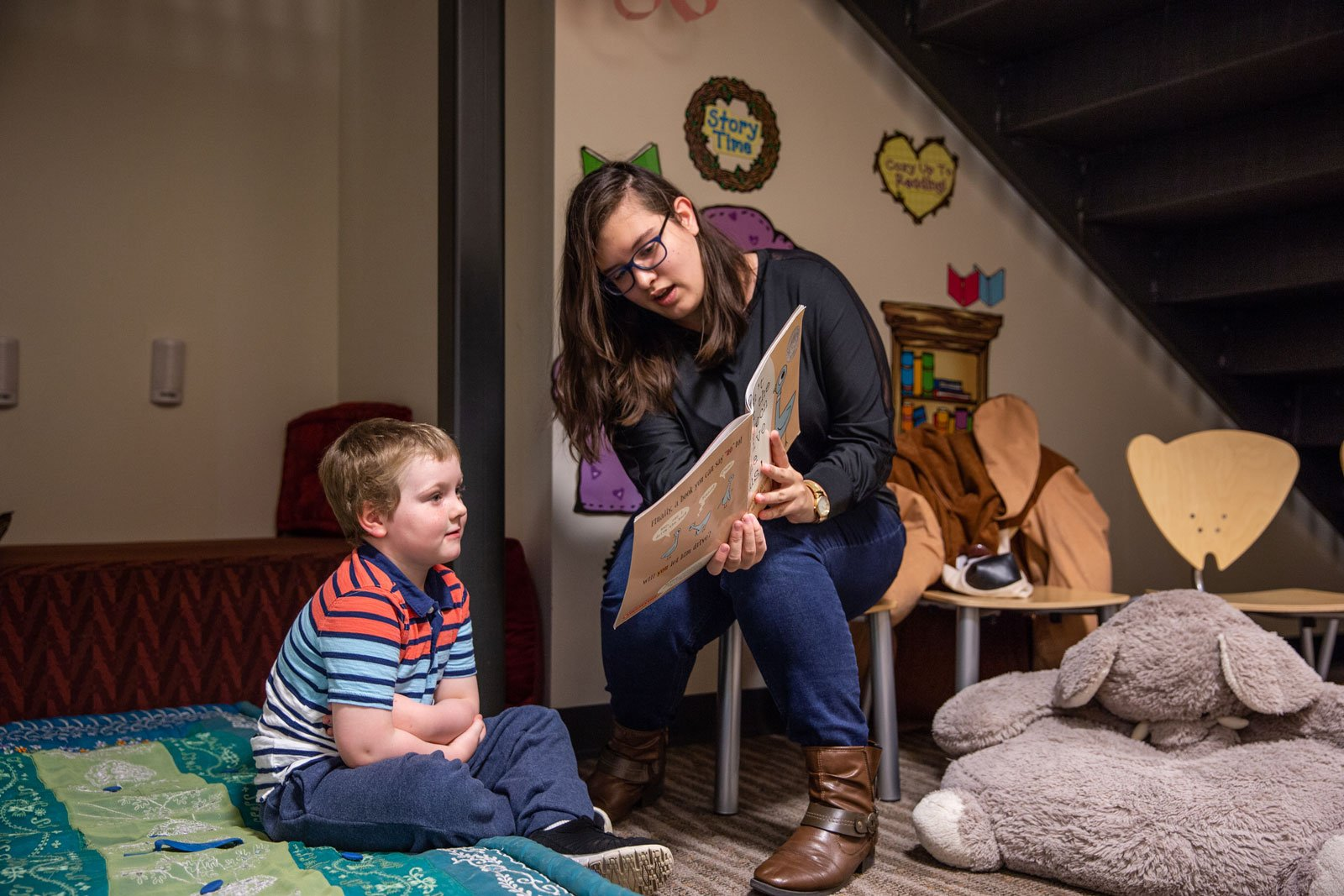 college student sitting on chair reading to small child sitting on rug
