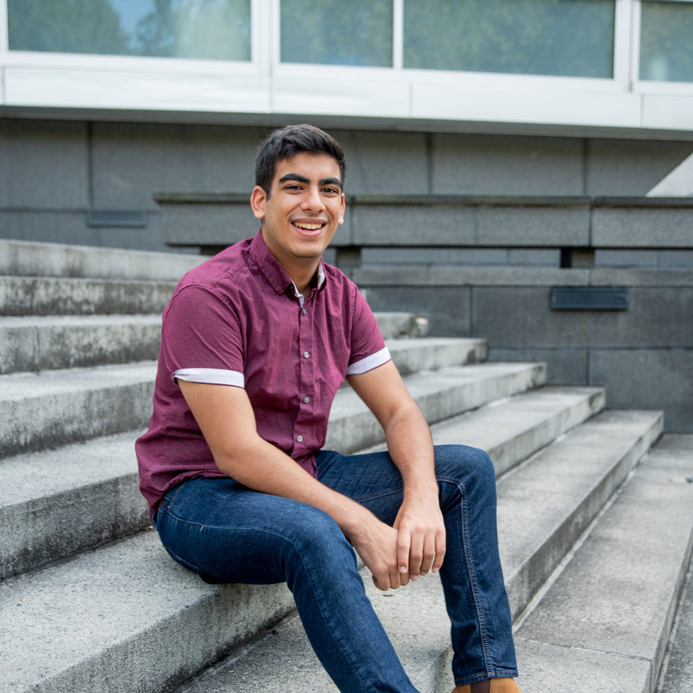Bhavik sits on the steps by Engineering Pond.