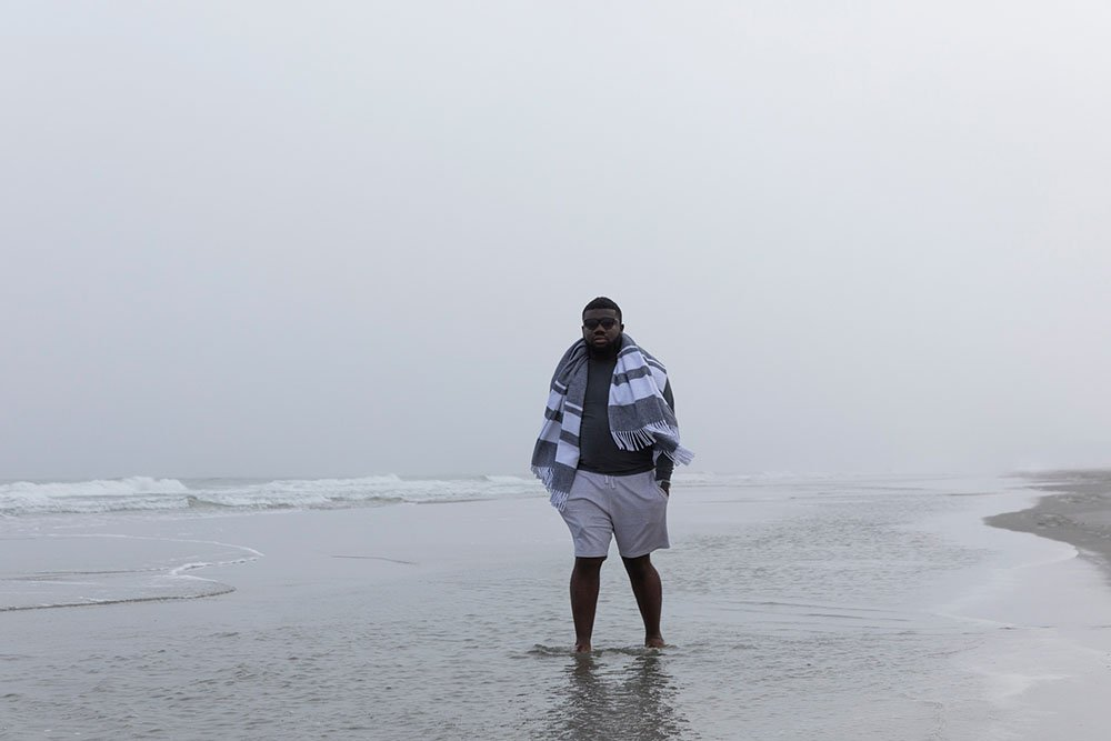 college student standing on the beach with a blanket