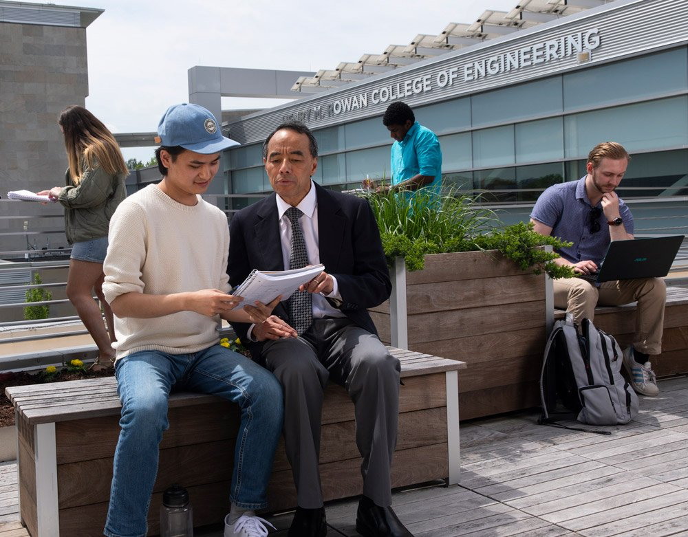 Assistant Dean of Engineering sits with student to study on engineering building terrace