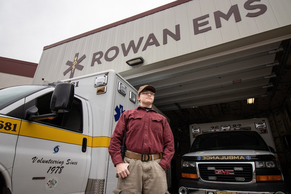 A student standing in front of the EMS ambulances