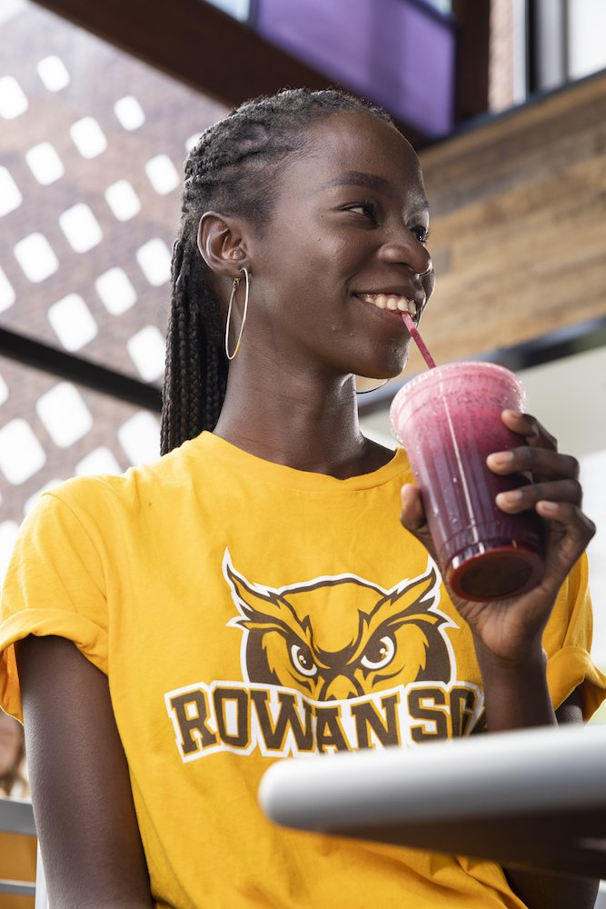 A close up portrait of a student drinking a smoothie.
