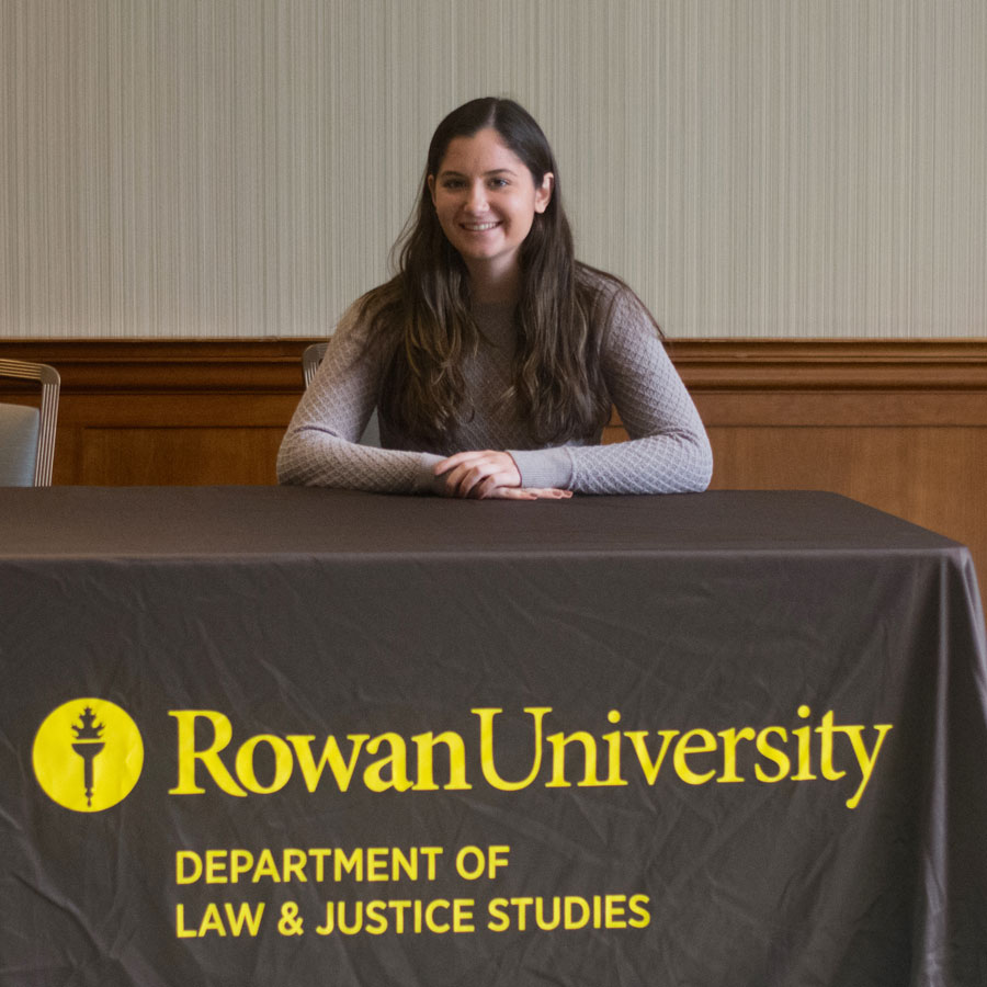 Ioli sits at a table with her arms folded on a brown tablecloth representing the law and justice major.