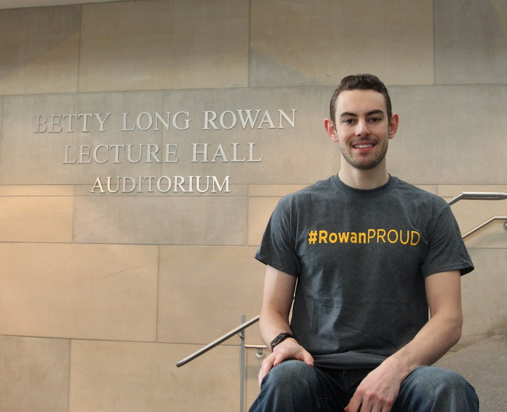 Jason F. posing in front of an auditorium hall