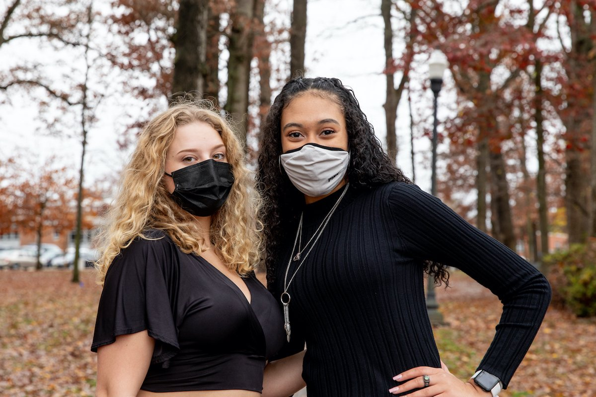 Two female students stand together while wearing masks.