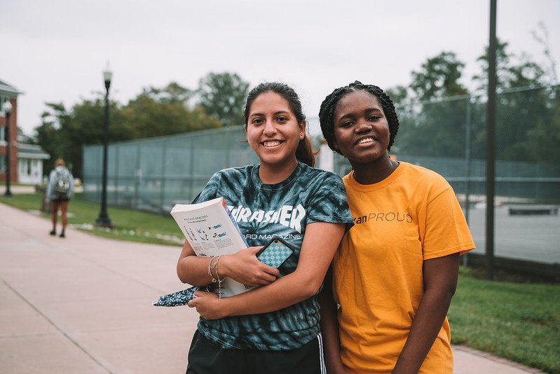 Two students smiling by the tennis courts.