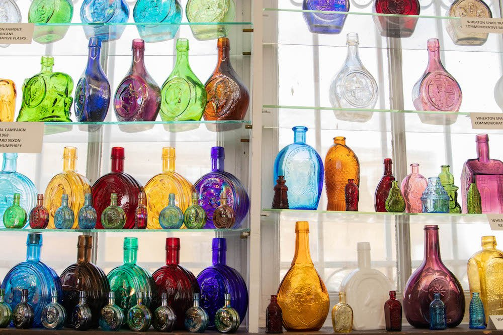 rows of colorful decorative glass vases on display