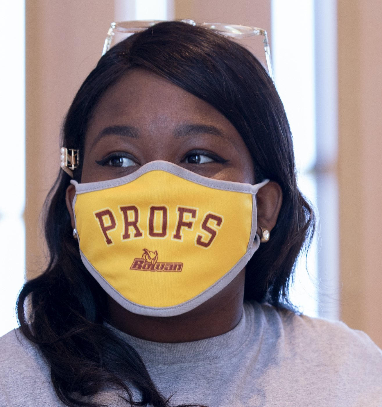 Girl gazing into the distance wearing a yellow Profs face mask.
